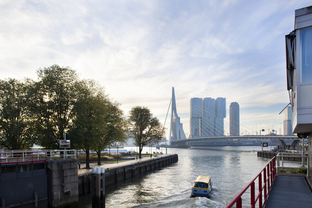 Early morning water taxi with the Erasmus bridge in the background in Rotterdam
