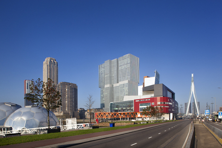 Kop van Zuid in Rotterdam with the red Luxor theatre in front of the huge Rem Koolhaas building and the Erasmus bridge on the right