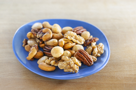 Close-up of a salted nuts mix on a blue dish