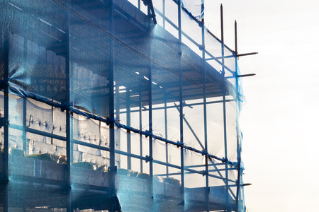 Blue scaffolding with safety netting in nice sunlight in the Netherlands Stockfoto