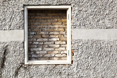 Brick wall behind a window frame in a plastered wall in Schoonhoven in the Netherlands