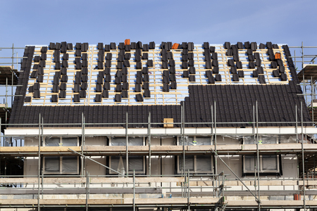 Roof under construction with stacks of black roof tiles in the Netherlands 스톡 콘텐츠