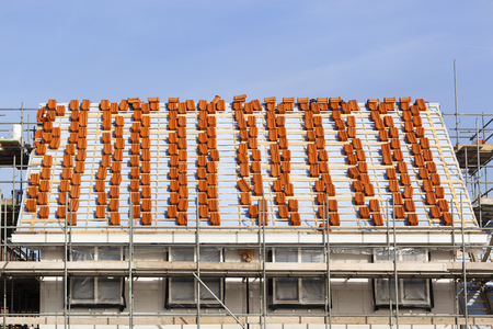 Roof under construction with stacks of red roof tiles in the Netherlands 스톡 콘텐츠