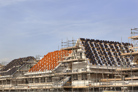 Roofs under construction at a construction site with stacks of red and black roof tiles in the Netherlands