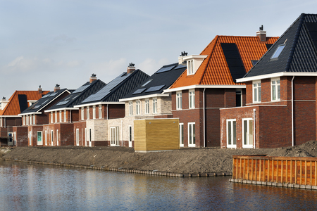 New built houses in a row with red and black roof tiles in the Netherlands 스톡 콘텐츠