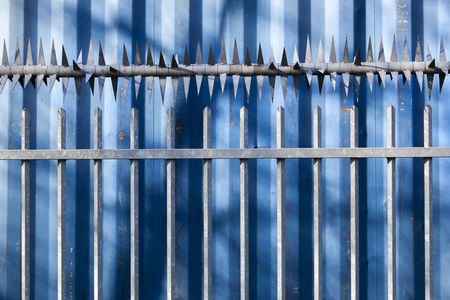 Blue cargo container behind a security fence with sharp spikes in the Netherlands