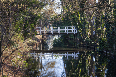 Small picturesque white wooden bridge in a park in the Netherlands