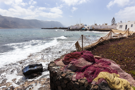 Fishing nets drying at the coast of village Caleta de Sebo on the island La Graciosa of Lanzarote