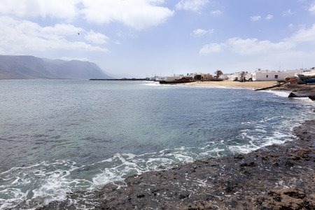 Rocks and white houses at the coast of Caleta de Sebo on the island La Graciosa of Lanzarote