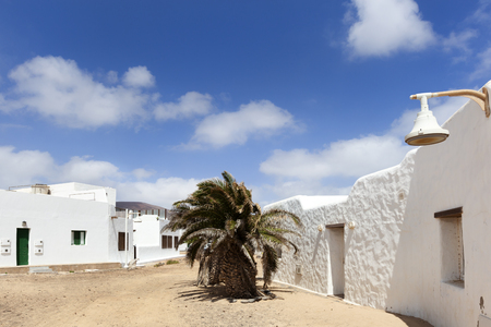 Empty street with sand and white houses and a palm tree in Caleta de Sebo on the island La Graciosa of Lanzarote