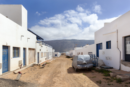 Empty street with sand and white houses and a car covered with plastic in Caleta de Sebo on the island La Graciosa of Lanzarote