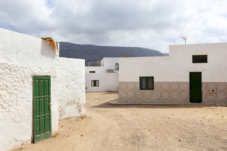 Empty street with sand and white houses in Caleta de Sebo on the island La Graciosa of Lanzarote