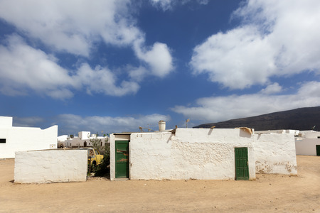 Empty street with sand and white houses and a boat in Caleta de Sebo on the island La Graciosa of Lanzarote 스톡 콘텐츠