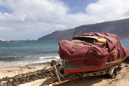 Old boat with plastic protection cover on a trailer on the island La Graciosa of Lanzarote