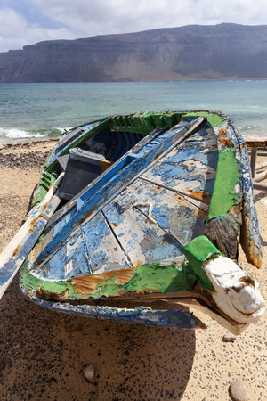 Dirty old weathered broken boat at the coast of Caleta de Sebo on the island La Graciosa of Lanzarote
