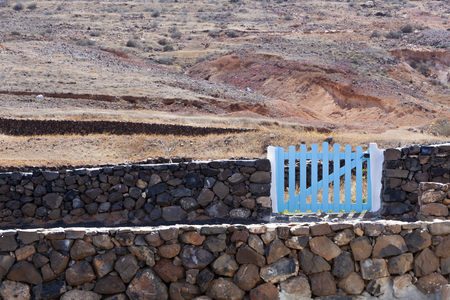 Volcanic stones and white concrete fence wall with blue wooden wicket gate typical on Lanzarote in Spain