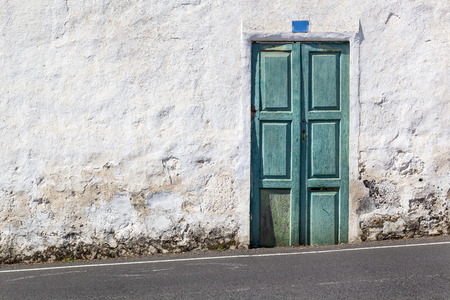 Old green door and a white plastered wall near a hillside asphalt road on Lanzarote in Spain 스톡 콘텐츠