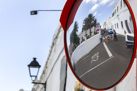 Roadblock by police because of the market in Teguise in Spain seen in a traffic security mirror