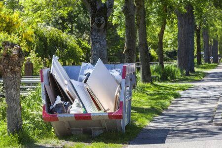 Skip with renovation waste under trees in Rotterdam in the Netherlands
