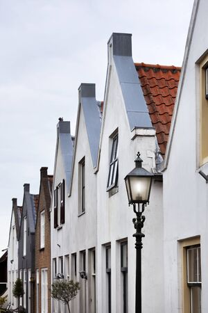 Street with historical facades and a lamppost in Goedereede in the Netherlands