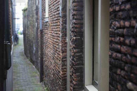 Narrow vintage alley with old brick walls in Dordrecht