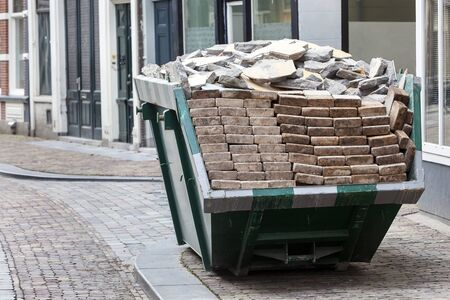 Neat industrial skip parked on the clean sidewalk full loaded with bricks and rubble in Dordrecht in the Netherlands Stockfoto