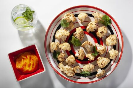 Spicy roasted cauliflower florets with mango pepper dipping sauce seen from above Stockfoto