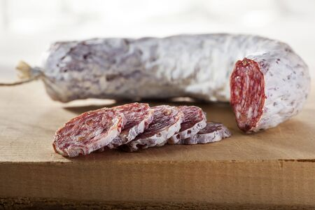 Sliced delicious dry sausage on a wooden cutting board Stockfoto