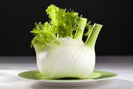 Fresh raw fennel on a plate on a white surface with a black background