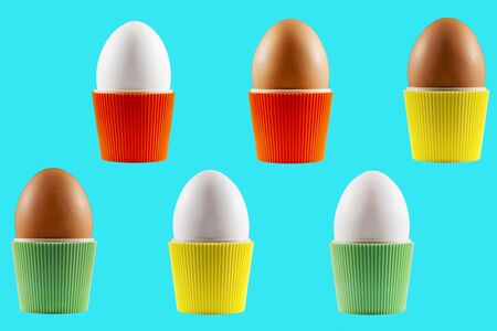 Colorful isolated Easter eggs in cups from the sixties presented with a blue background