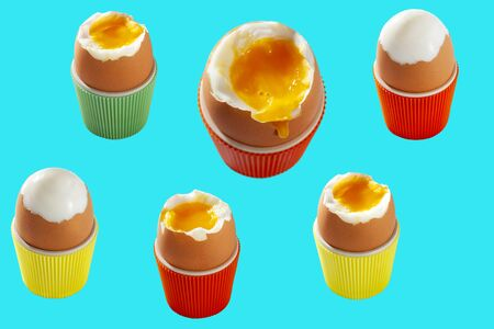 Isolated soft boiled Easter eggs in colorful cups from the sixties presented with a blue