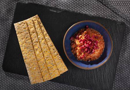 Muhammara with and crackers for dipping on slate seen from above 版權商用圖片