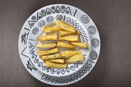 Crispy traditional parsnip chips with herbs on a dish