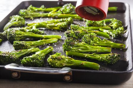 Broccoli roasted on an oven dish and a red pepper mill 版權商用圖片