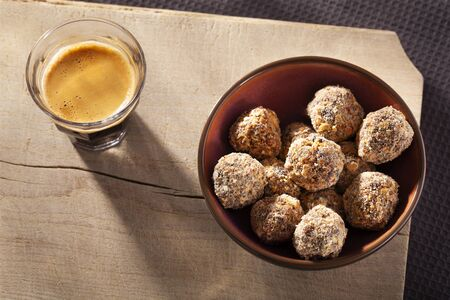 Sweet handmade fruit balls covered with oats and a cup espresso seen from above