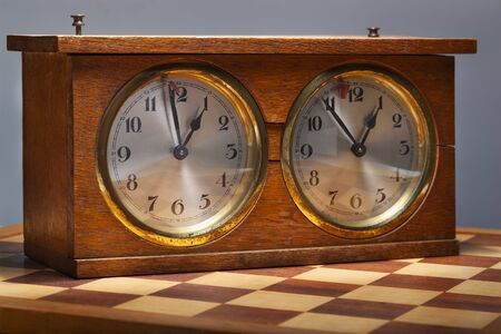 Old wooden vintage chess clock and a chessboard 版權商用圖片