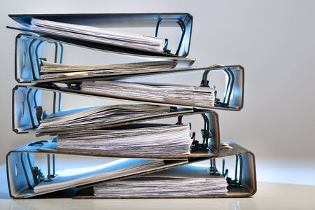 Stack of office folders with archived paperwork in red light