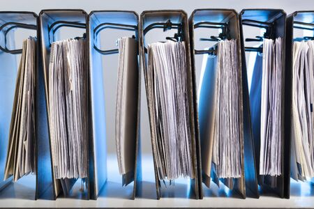 Office folders with archived paperwork in a row in blue light