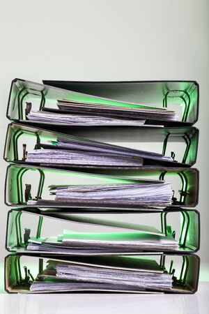 Stack of files with archived paperwork in green light. 版權商用圖片