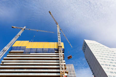 Construction site with two cranes hoisting construction material in Rotterdam in the Netherlands Archivio Fotografico