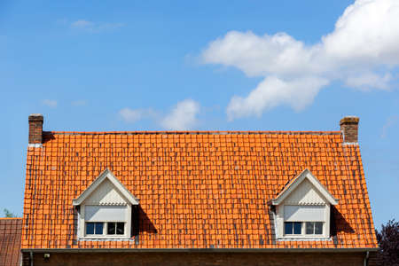 Symmetric red tiled roof with two dormers with rolling shutters and two chimneys in the Netherlands Stockfoto