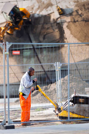 Rotterdam, Netherlands - September 11, 2020: Construction worker with a wacker smoking a cigar and the reflection of an excavator and a heap of sand in the mirrors of museum Boijmans van Beuningen depot building in Rotterdam, the Netherlands