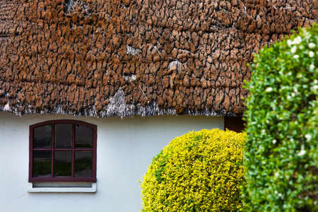 Farm window under an old thatched roof overgrown with moss Stockfoto