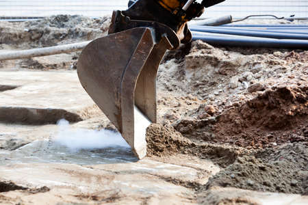 Closeup of an excavator producing smoke while scraping sand from concrete on an construction site Stockfoto