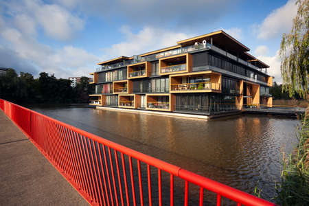 Apartment building built in water in Rotterdam seen from a bridge with red railing in the Netherlands Stockfoto