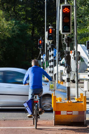 Cyclist waiting for red light of a temporary traffic light because of roadworks in Rotterdam in the Netherlands Stockfoto