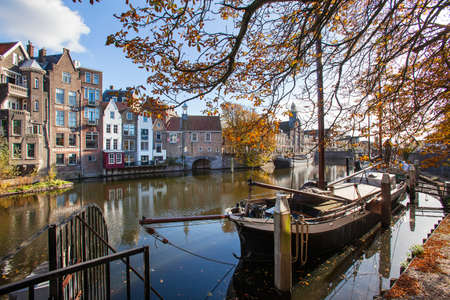 Rotterdam, Netherlands - November 4, 2020: Historic Delfshaven with traditional houseboats moored near the quay in autumn