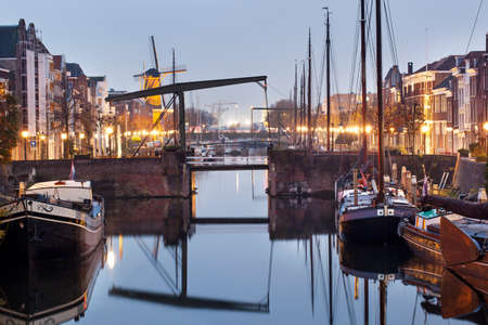 Rotterdam, Netherlands - November 10, 2020: Historical house boats moored in Delfshaven in Rotterdam at twilight Editorial