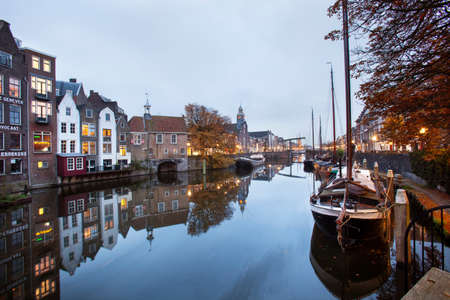 Rotterdam, Netherlands - November 10, 2020: Historical house boats moored in Delfshaven in Rotterdam at twilight Redactioneel
