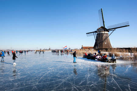 Zevenhuizen, Netherlands - February 13, 2021: Dutch winter landscape with Ice skaters on the Rottemeren near a windmill Editorial